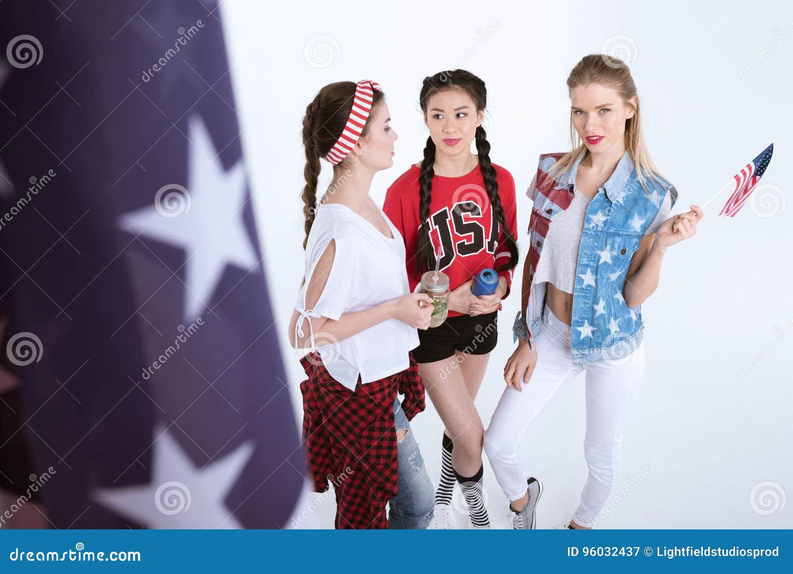 Uśmiechnięte dziewczyny opowiada napoje odizolowywających na bielu i pije z flaga amerykańską