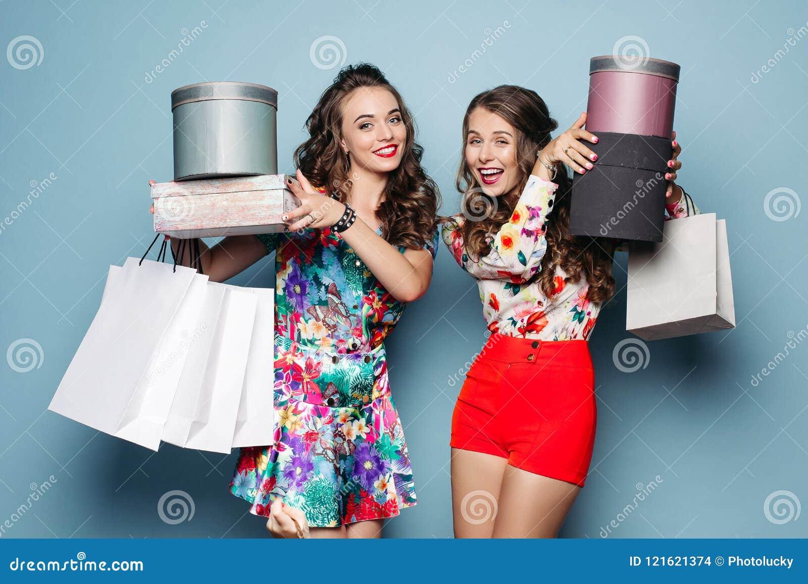 Uśmiechnięte dziewczyny w kolorowych ubraniach z wiele torbami po robić zakupy