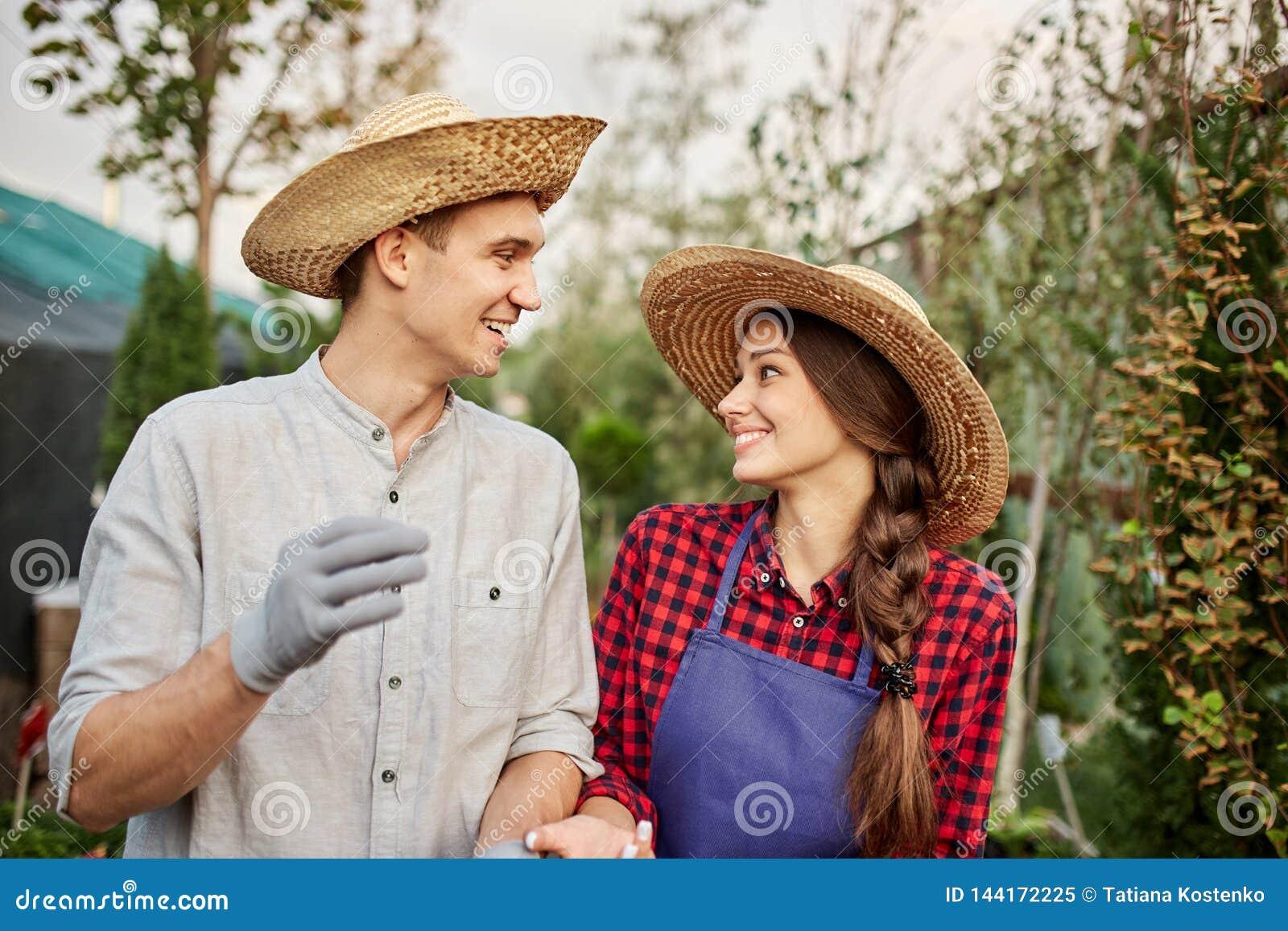 Uśmiechnięte faceta i dziewczyny ogrodniczki w słomiani kapelusze patrzeją do siebie w ogródzie na słonecznym dniu