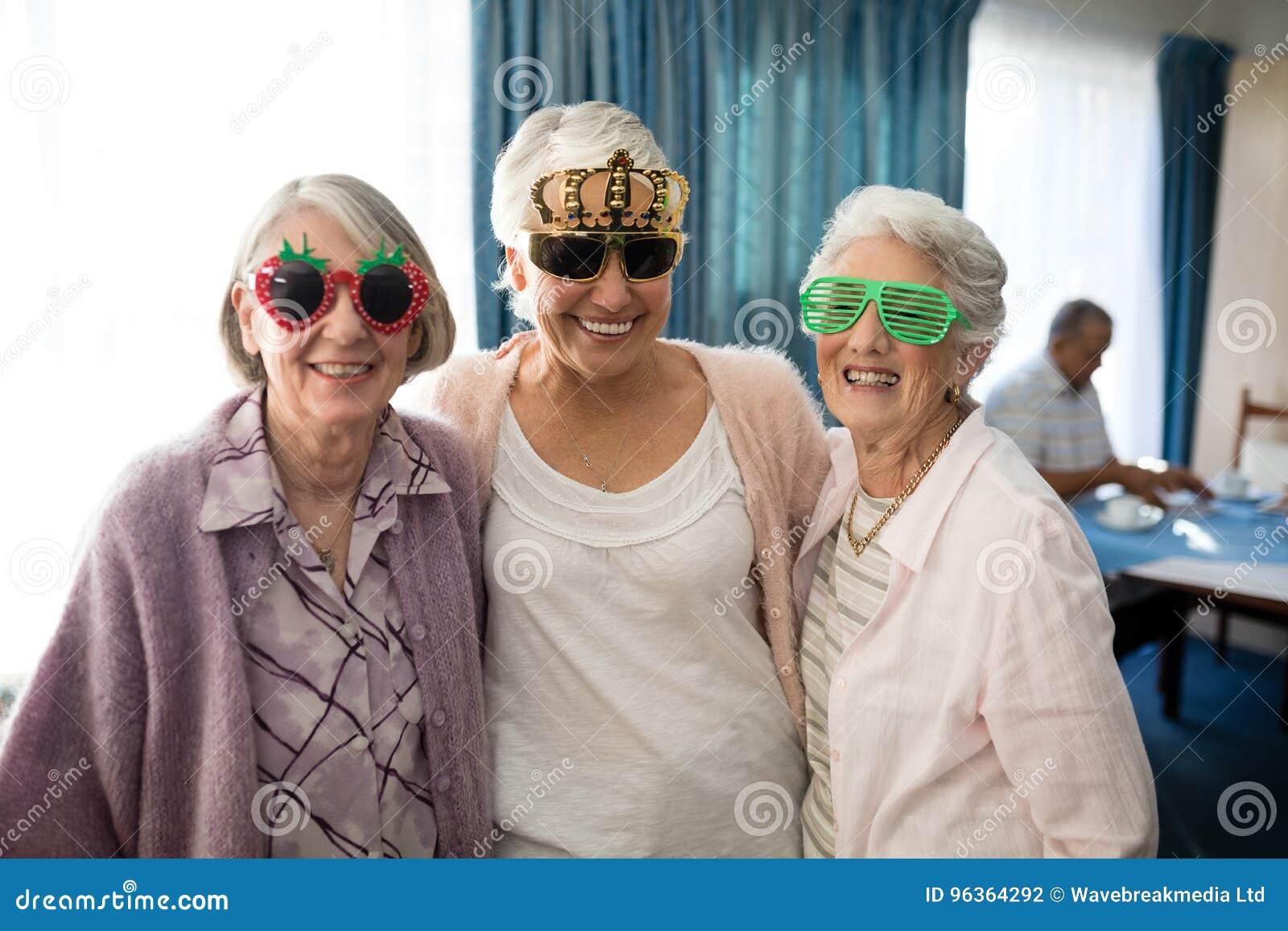 Uśmiechnięte starsze kobiety jest ubranym odkrywczość szkła