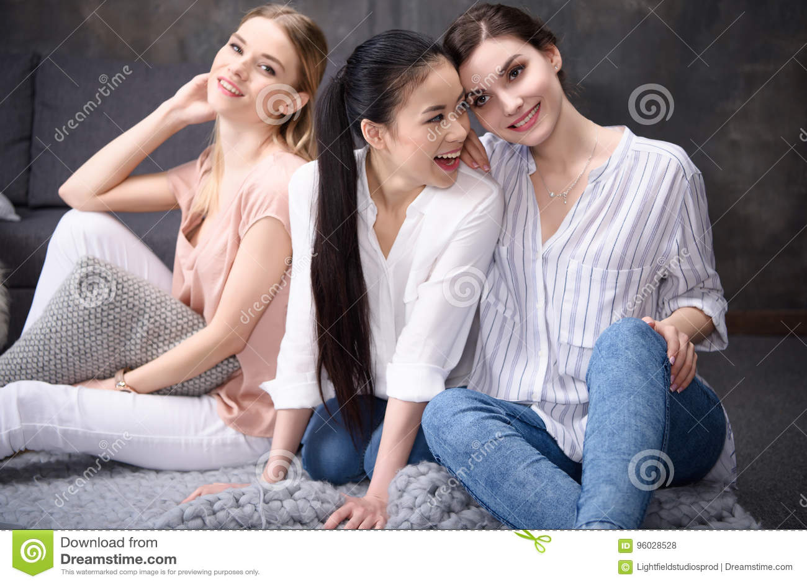 Uśmiechnięte wieloetniczne dziewczyny siedzi na podłoga wpólnie