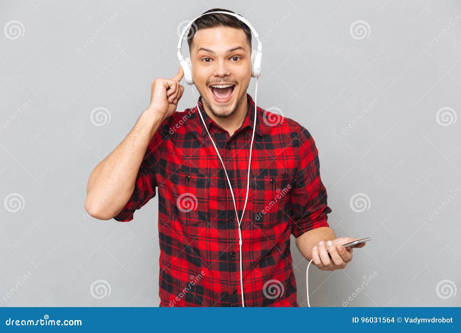 Uśmiechniętego młodego człowieka słuchająca muzyka z hełmofonami