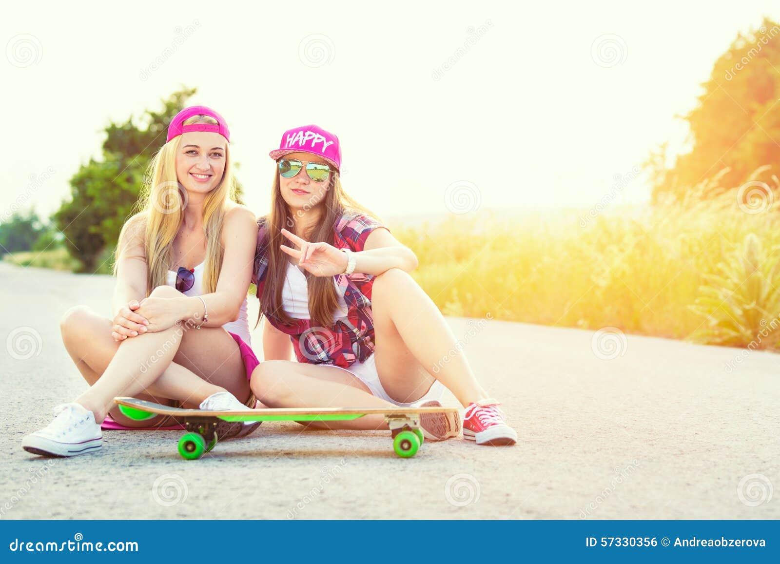 Uśmiechniętego modnisia nastoletni przyjaciele z deskorolka, colorised wizerunek z sunflare
