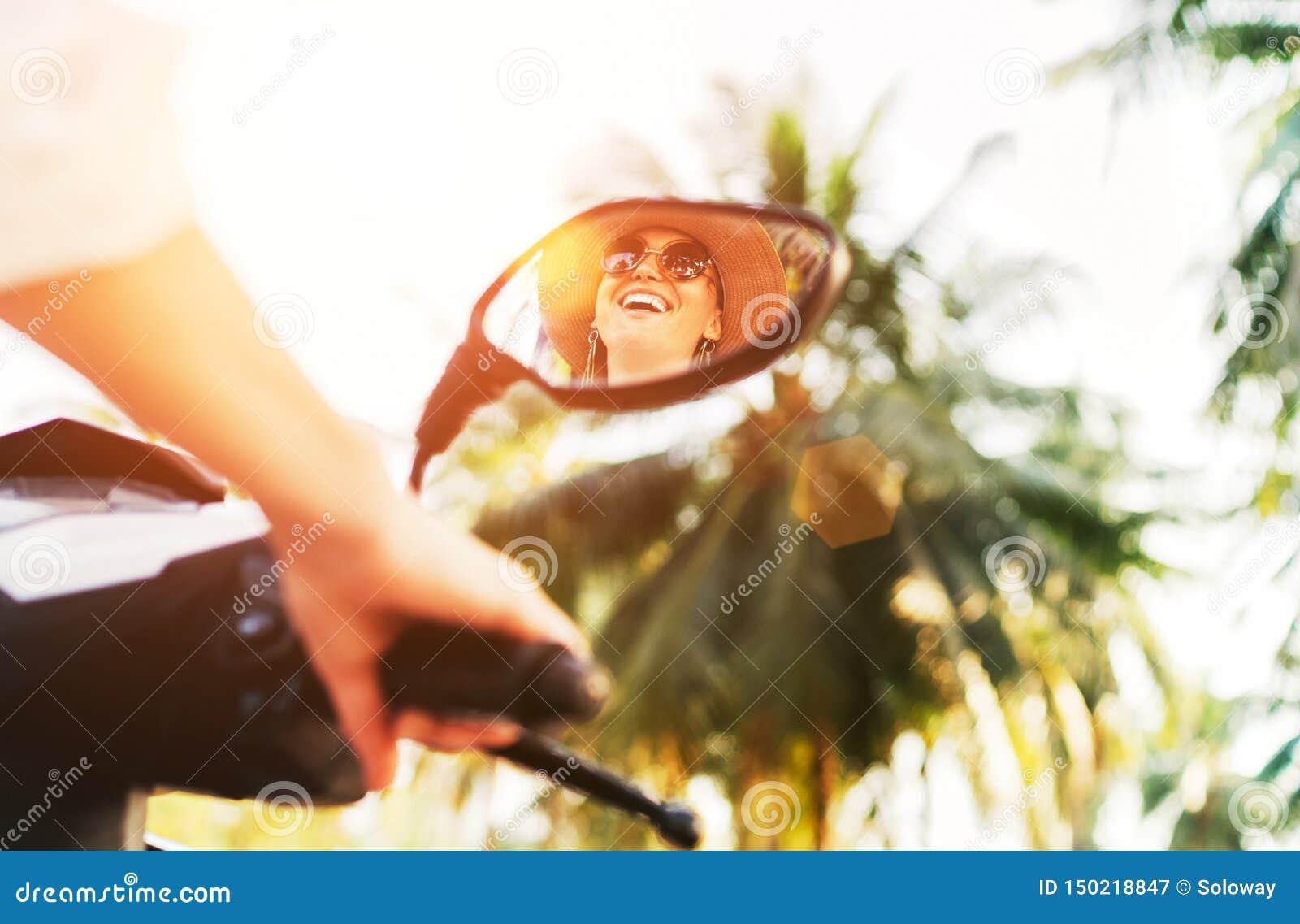 Uśmiechniętej kobiety jeździecki motocykl odzwierciedlający w rearview lustrze z olśniewającymi sunrays na tle Rozochoceni ludzie