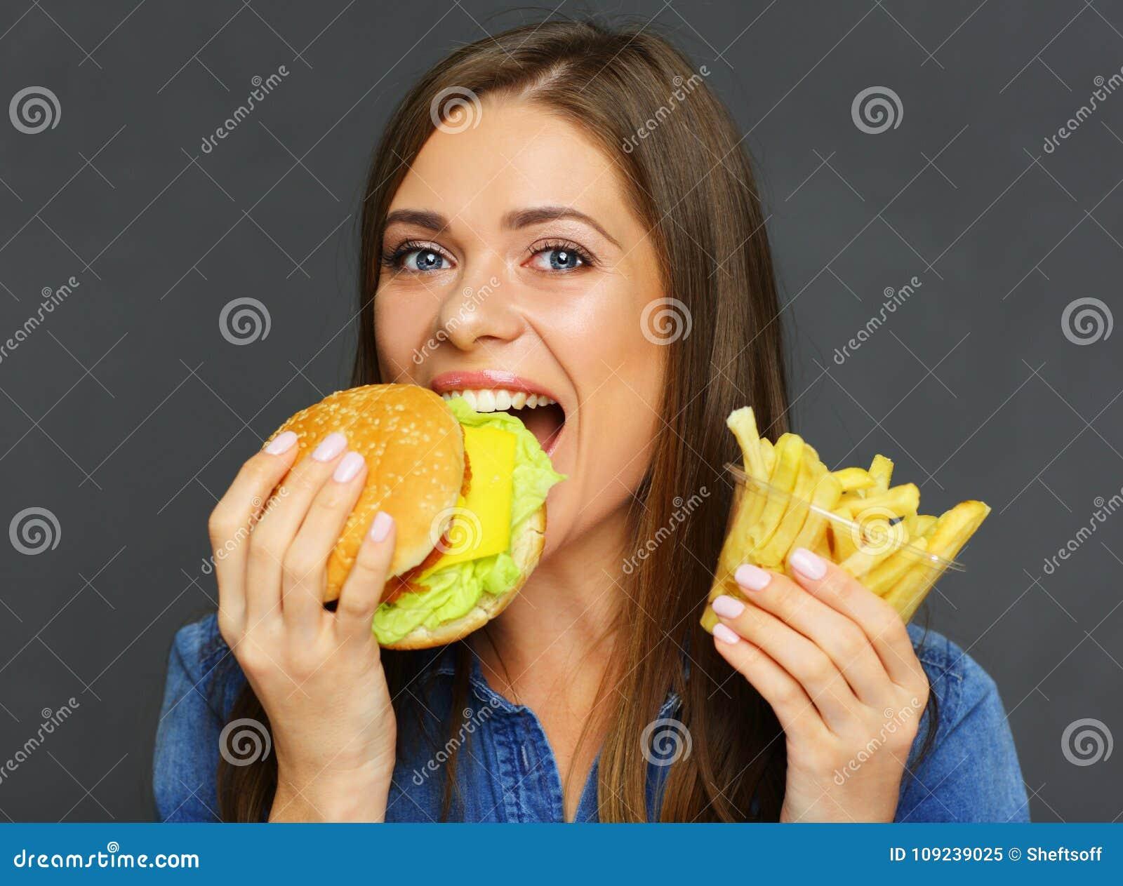 Uśmiechniętej kobiety zjadliwy hamburger i mienie francuscy dłoniaki, fast food