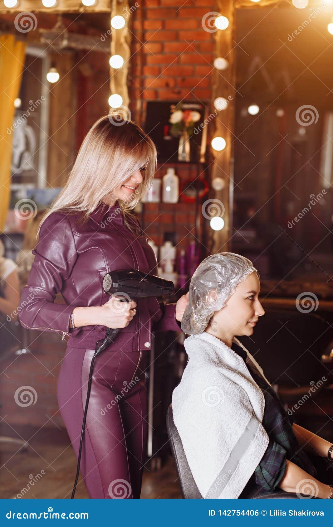 Uśmiechnięty ładny fachowy fryzjer pracuje z żeńskiego klienta mienia fachową włosianą suszarką w włosianym salonie Piękno i ludz