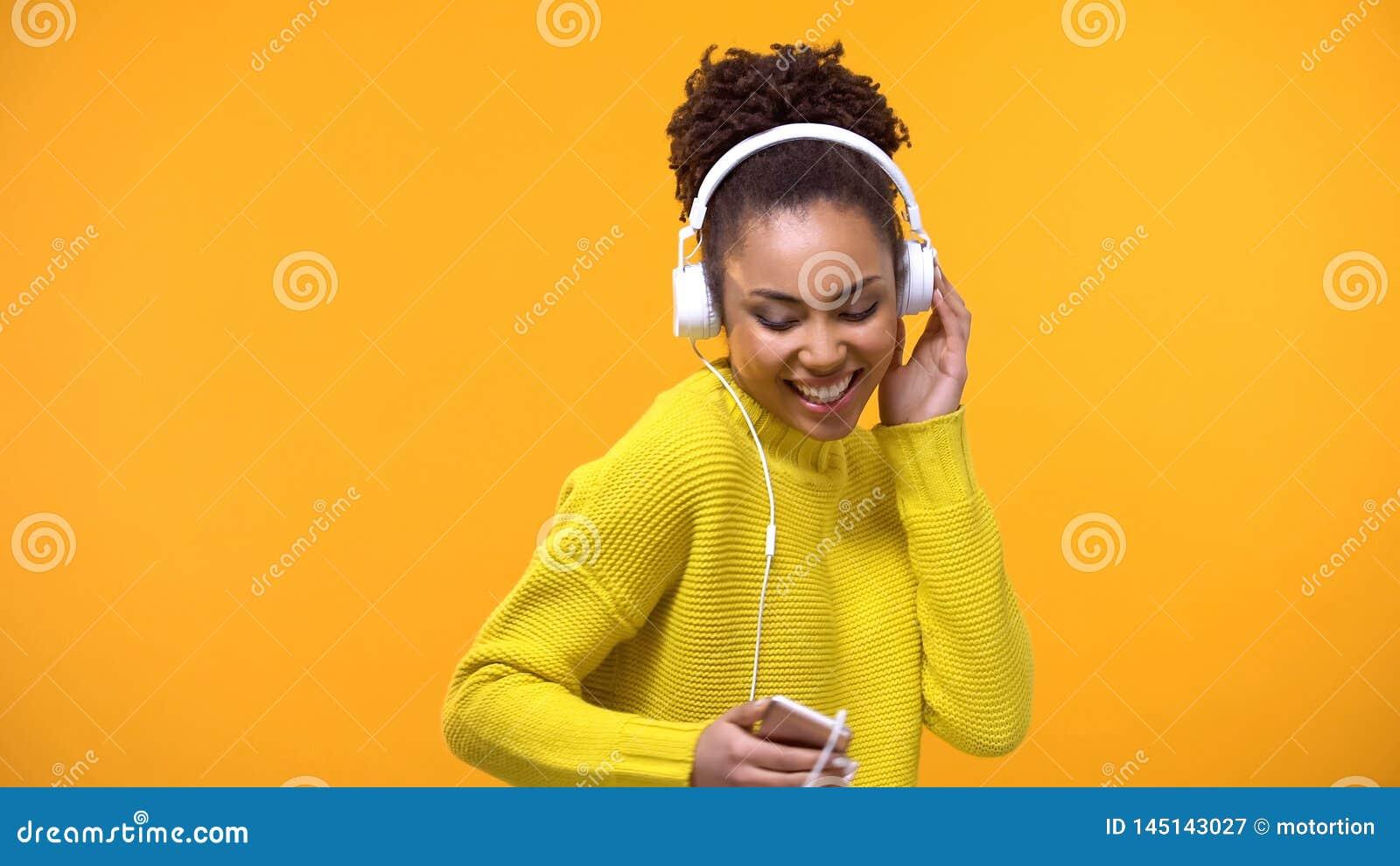 Uśmiechnięty żeński słuchanie ulubiona melodia w białych hełmofonach, technologia