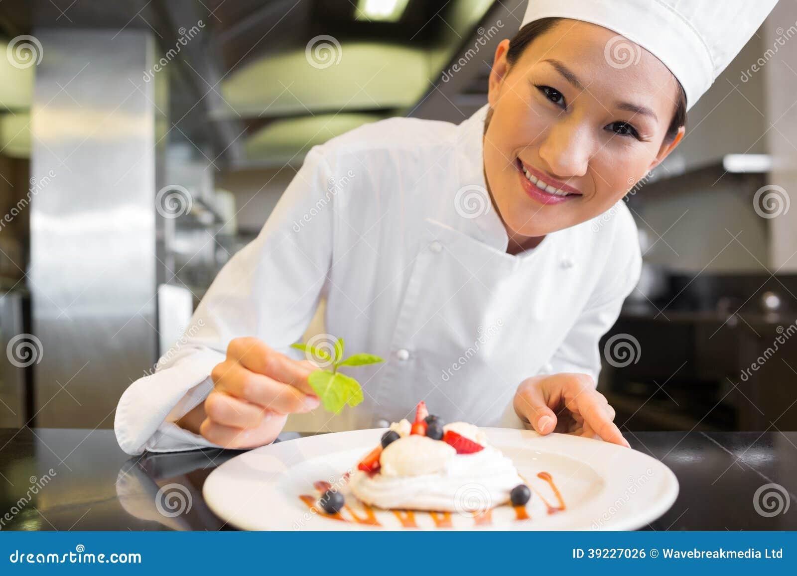 Uśmiechnięty żeński szefa kuchni garnirowania jedzenie w kuchni