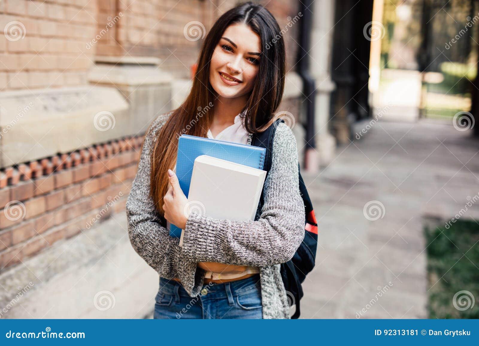 Uśmiechnięty żeński uczeń w czarnych eyeglasses z falcówkami i torbie w plecy