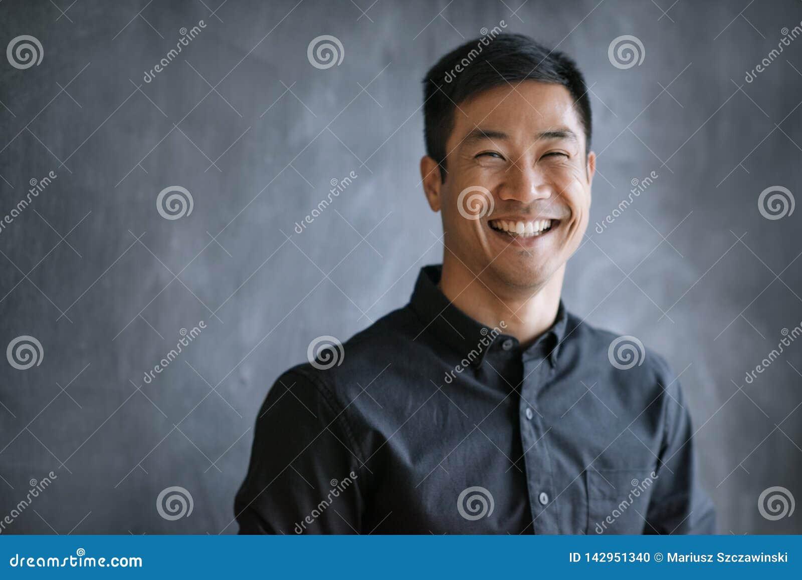 Uśmiechnięty Azjatycki biznesmen stoi bezczynnie chalkboard w biurze