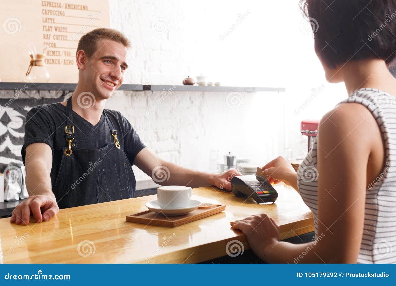 Uśmiechnięty barman bierze zapłatę od klienta przy kontuarem sklep z kawą