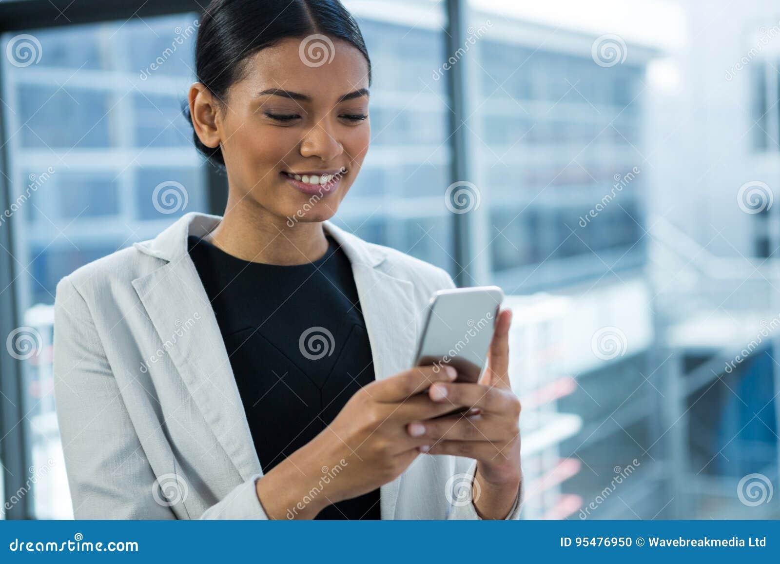 Uśmiechnięty bizneswoman Używa telefon komórkowego