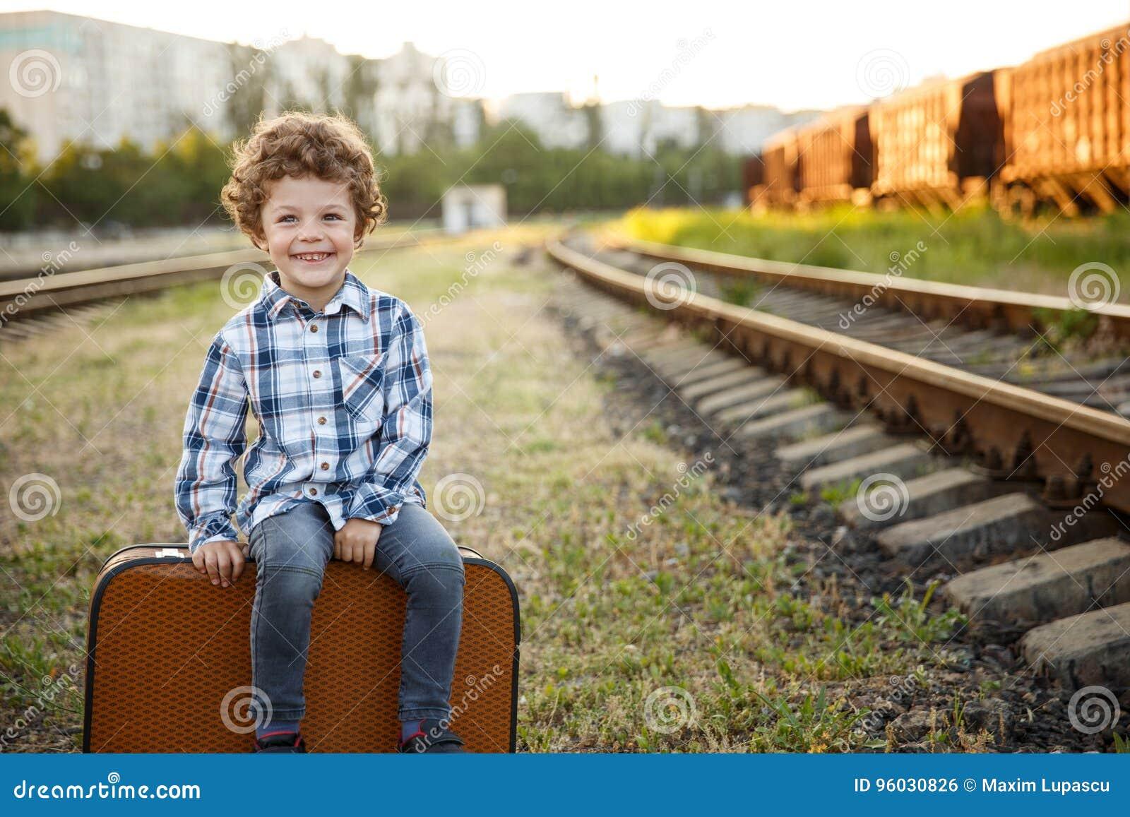 Uśmiechnięty dziecka obsiadanie na walizce outside