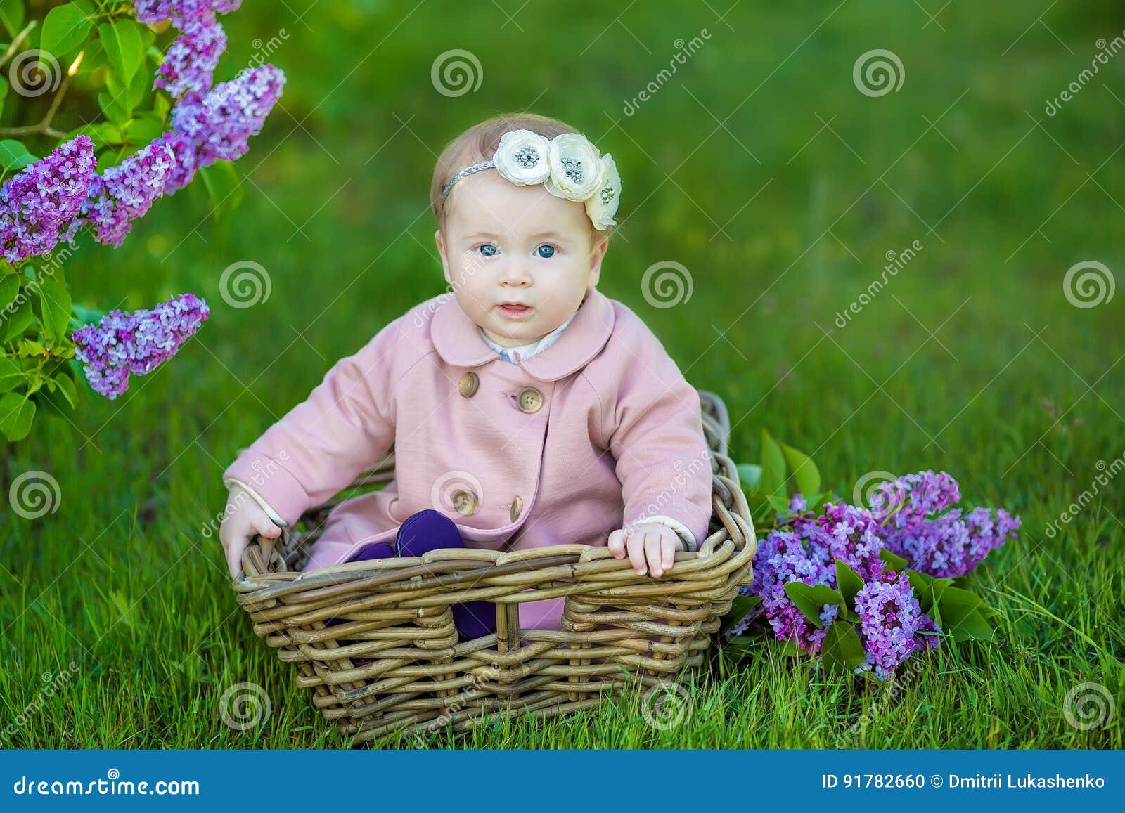 Uśmiechnięty dziewczynki 1-2 roczniak jest ubranym kwiatu wianek, trzyma bukiet bez outdoors patrzeć kamerę lato wiosny czas