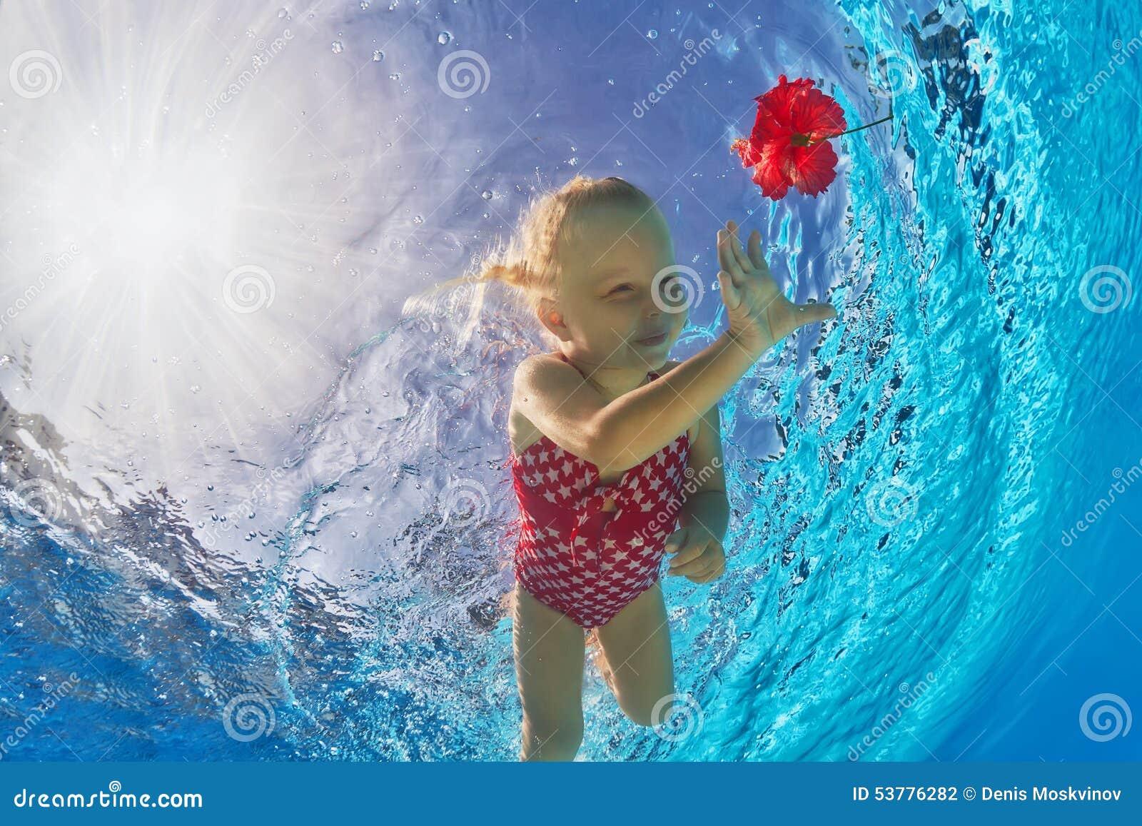 Uśmiechnięty dziewczyny pływać podwodny w basenie dla tropikalnego czerwonego kwiatu