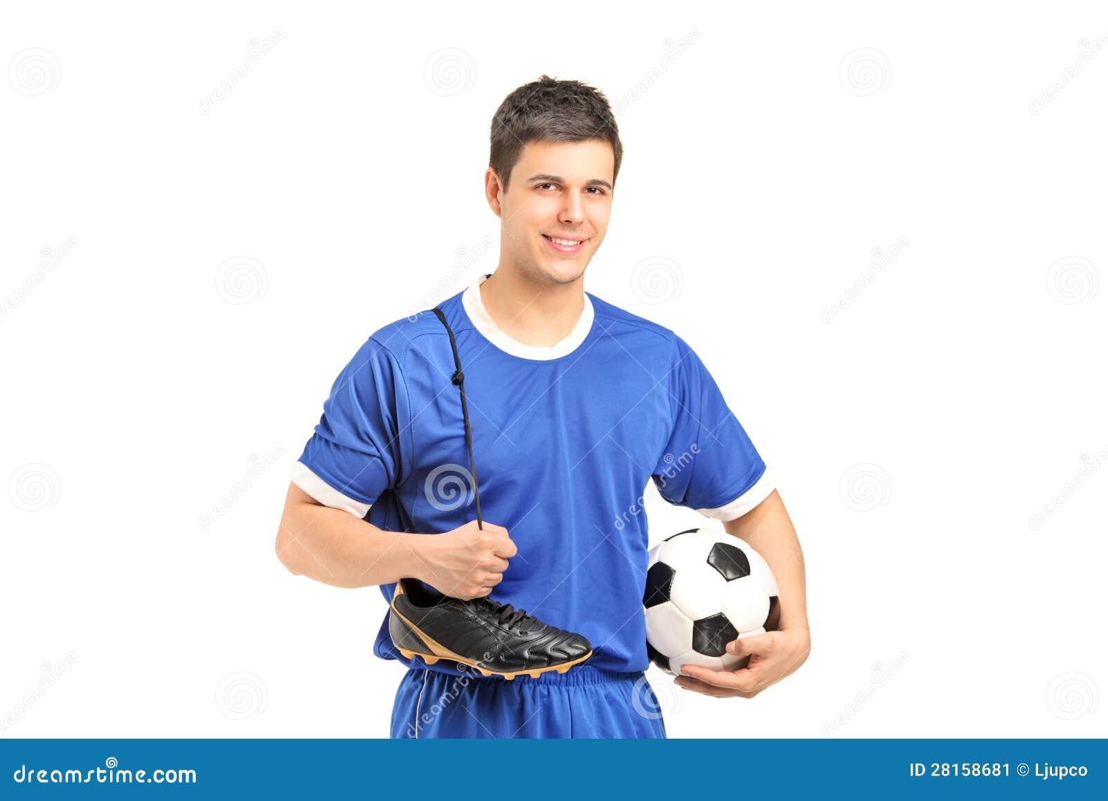 Uśmiechnięty futbolista trzyma piłki nożnej stopę i buty w sport odzieży