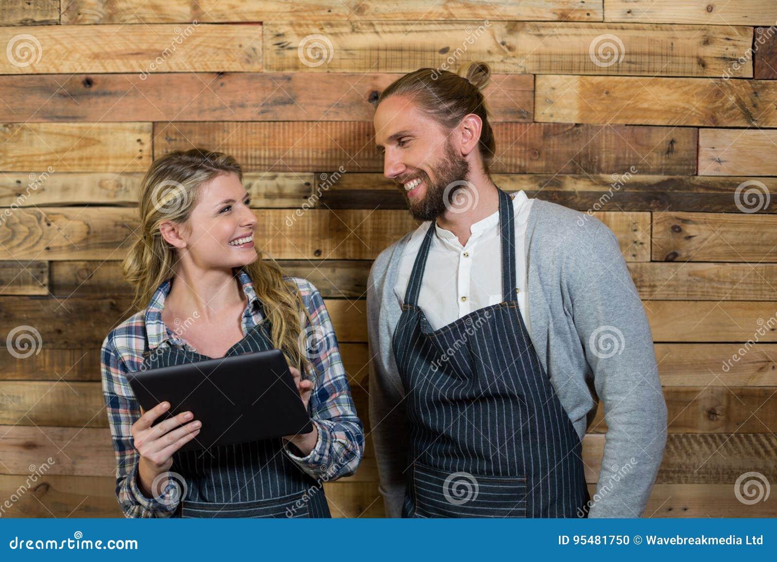 Uśmiechnięty kelner i kelnerka używa cyfrową pastylkę przeciw drewnianej ścianie