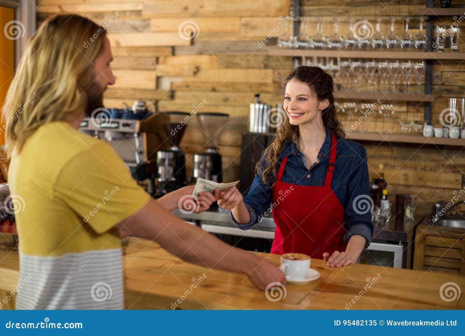 Uśmiechnięty klient płaci rachunek gotówką przy kontuarem