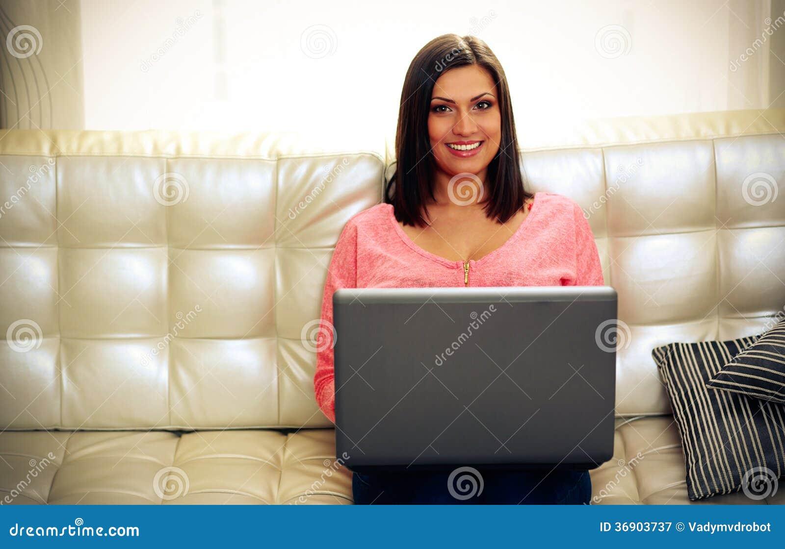 Uśmiechnięty kobiety obsiadanie na kanapie z laptopem