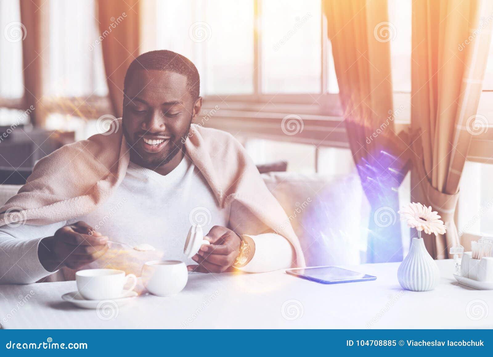 Uśmiechnięty mężczyzna kładzenia cukier w herbatę