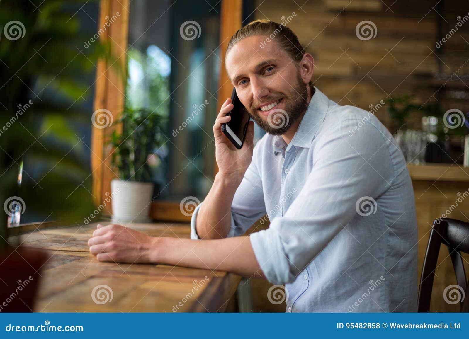 Uśmiechnięty mężczyzna opowiada na telefonie komórkowym przy café