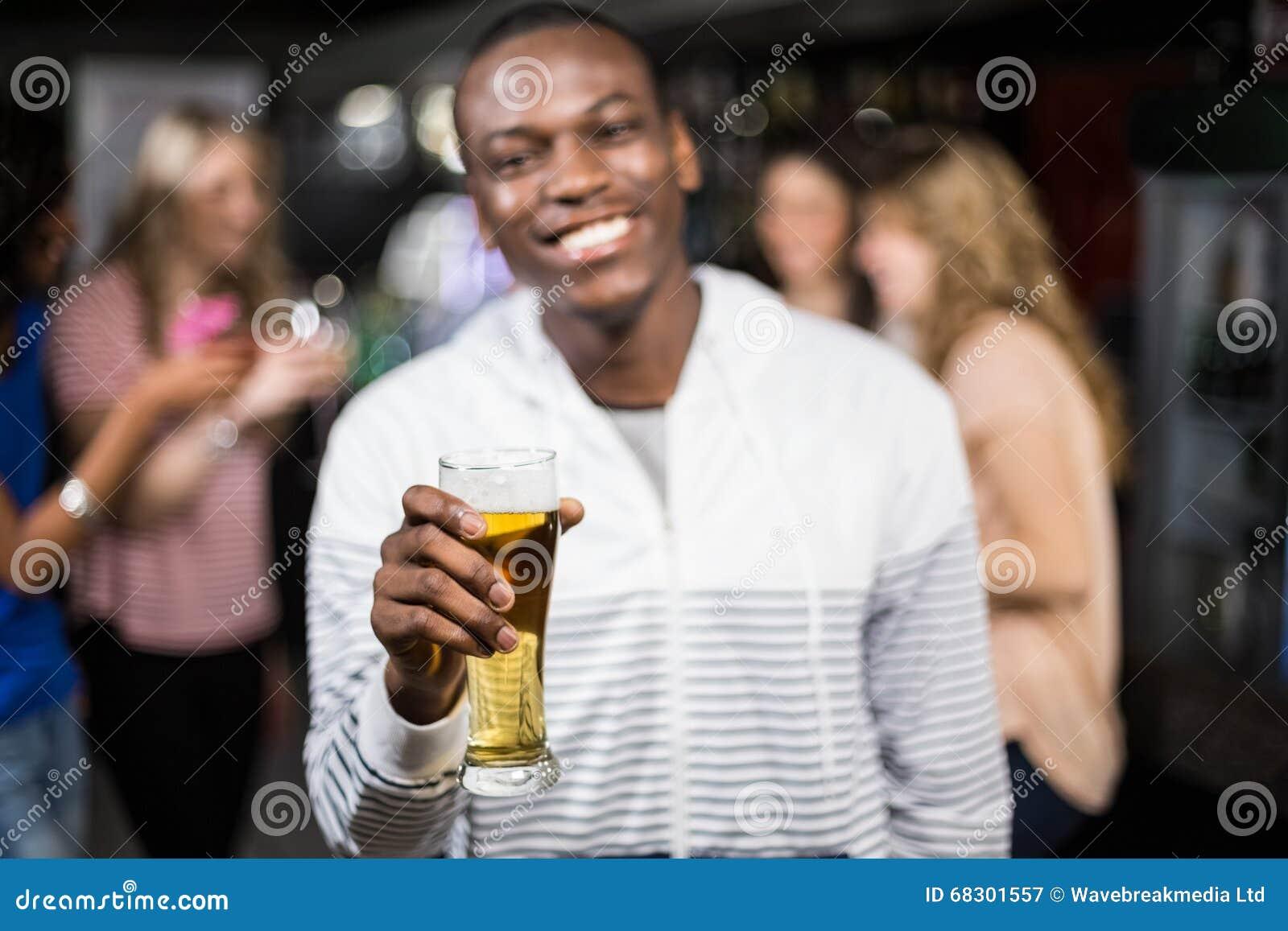 Uśmiechnięty mężczyzna pokazuje piwo z jego przyjaciółmi