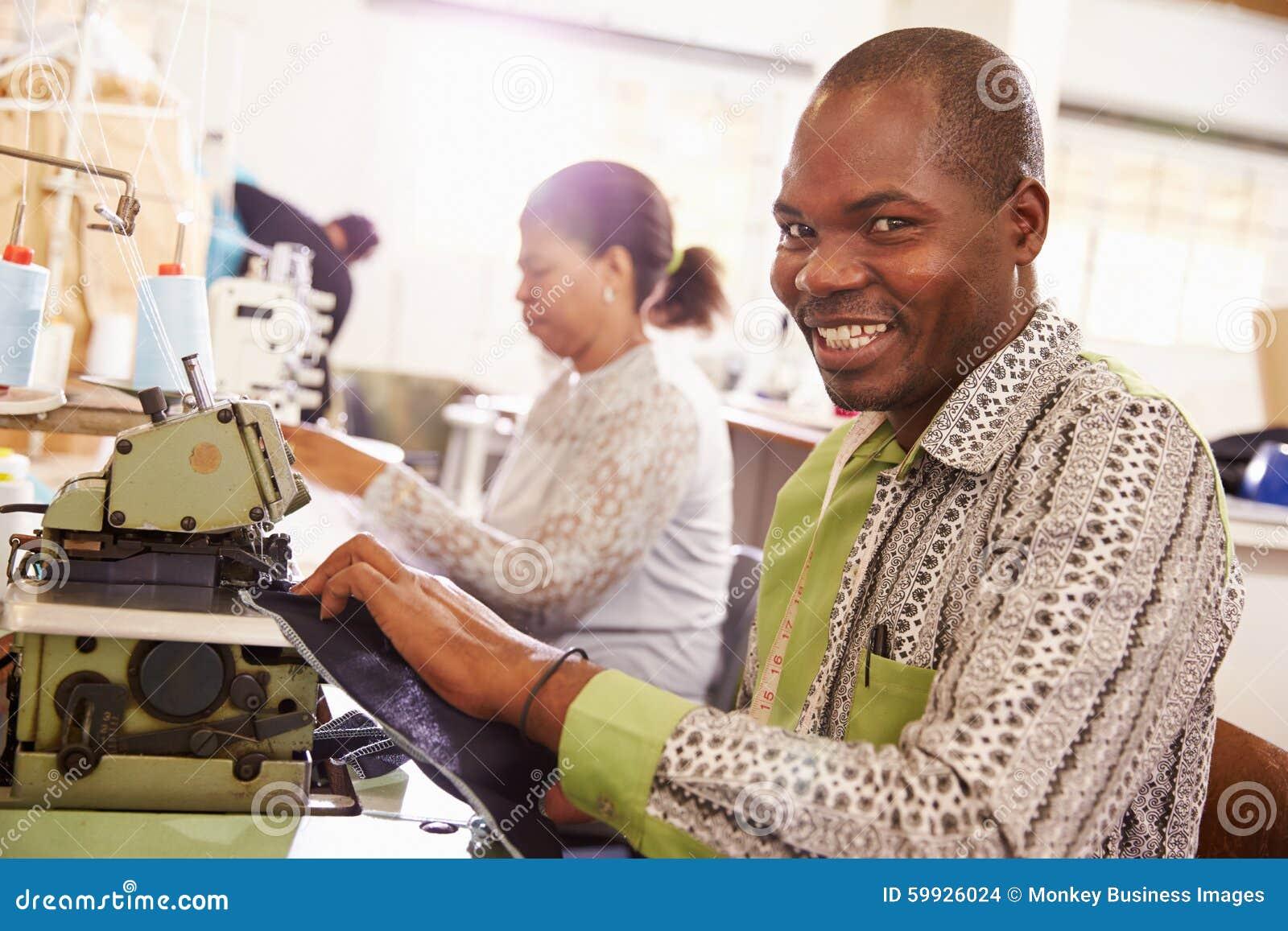 Uśmiechnięty mężczyzna szy przy społeczność warsztatem, Południowa Afryka