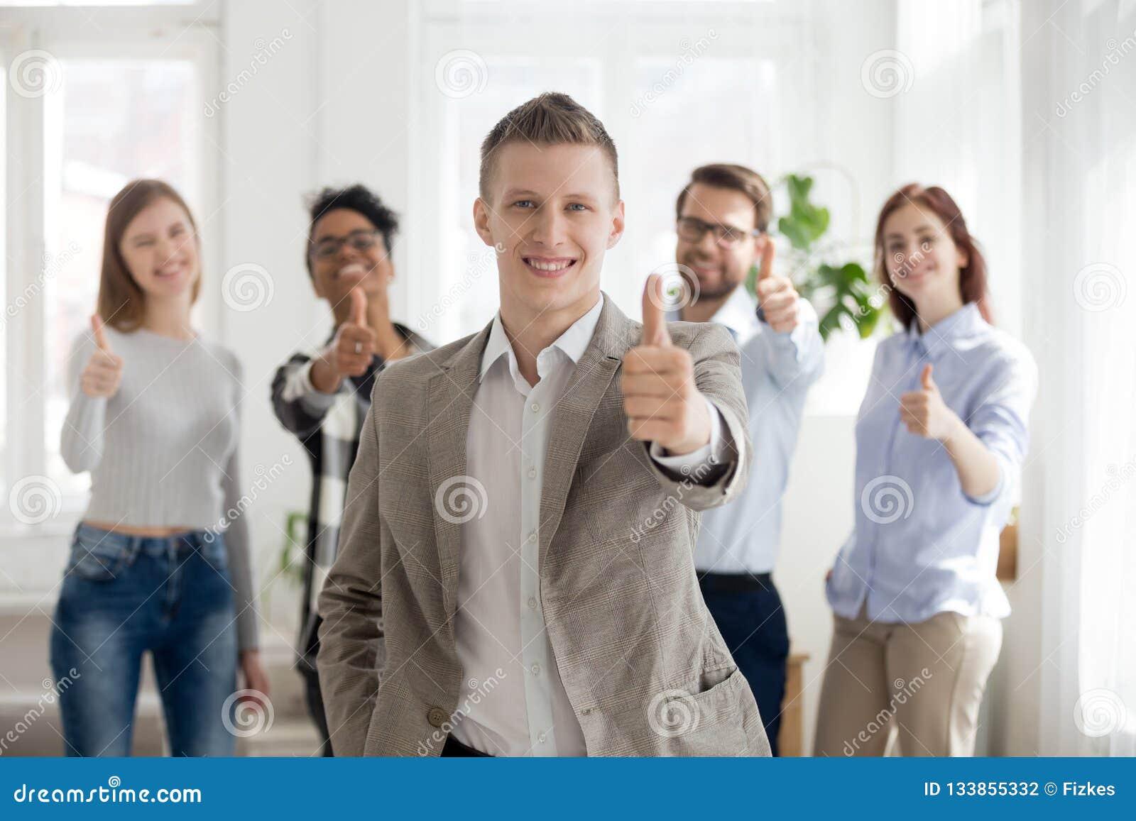 Uśmiechnięty męski pracownik z różnorodnymi drużynowymi przedstawienie aprobatami