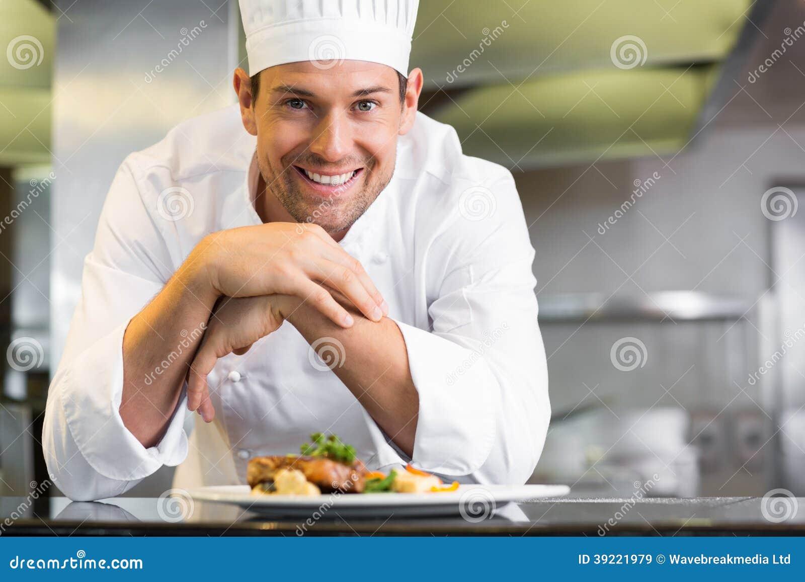 Uśmiechnięty męski szef kuchni z gotującym jedzeniem w kuchni