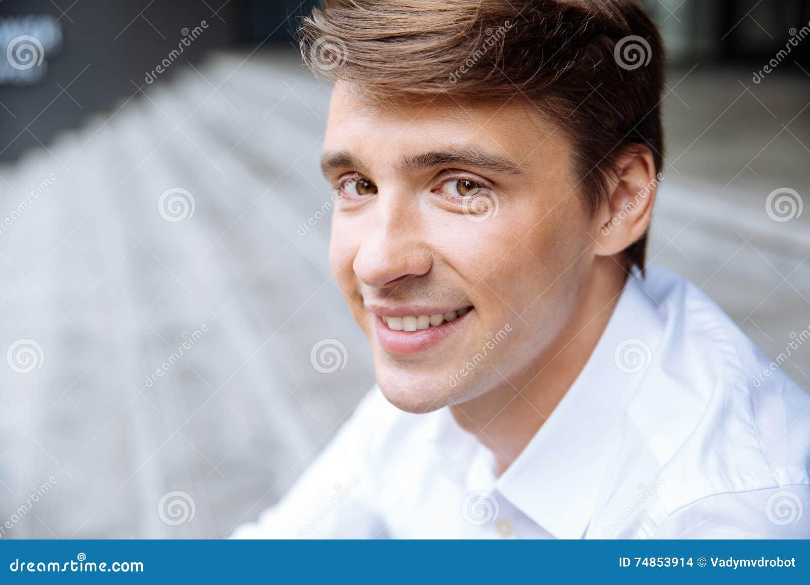 Uśmiechnięty młody biznesmen w białym koszulowym obsiadaniu outdoors