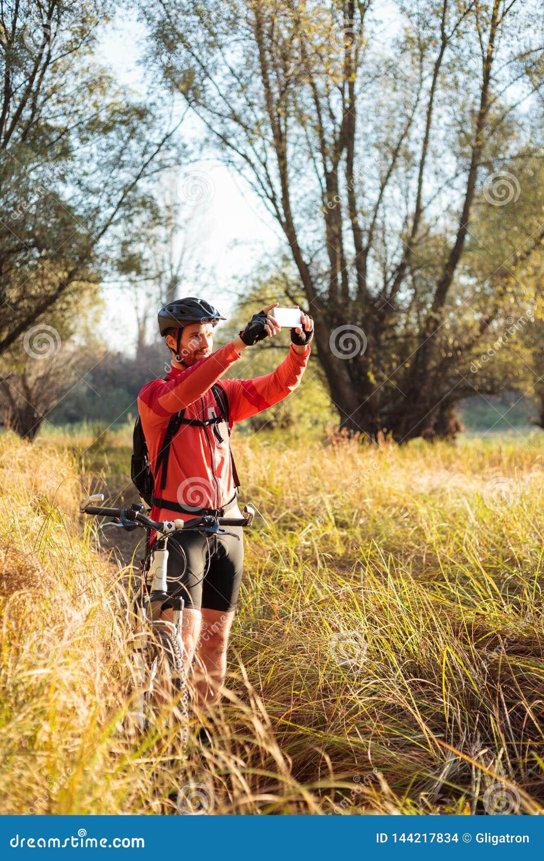 Uśmiechnięty młody brodaty halny rowerzysta bierze fotografie piękna sceneria