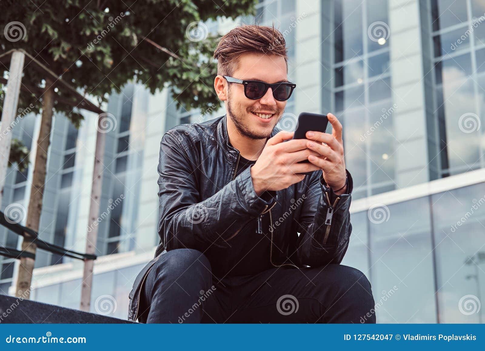 Uśmiechnięty młody człowiek w okularach przeciwsłonecznych z eleganckim włosy ubierał w czarnej skórzanej kurtce używać smartphon