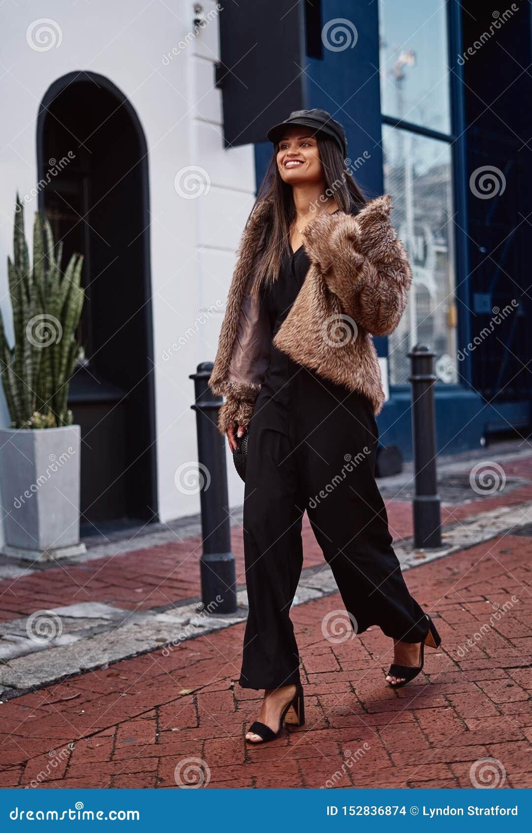 Uśmiechnięty mody młodej kobiety odprowadzenie w mieście