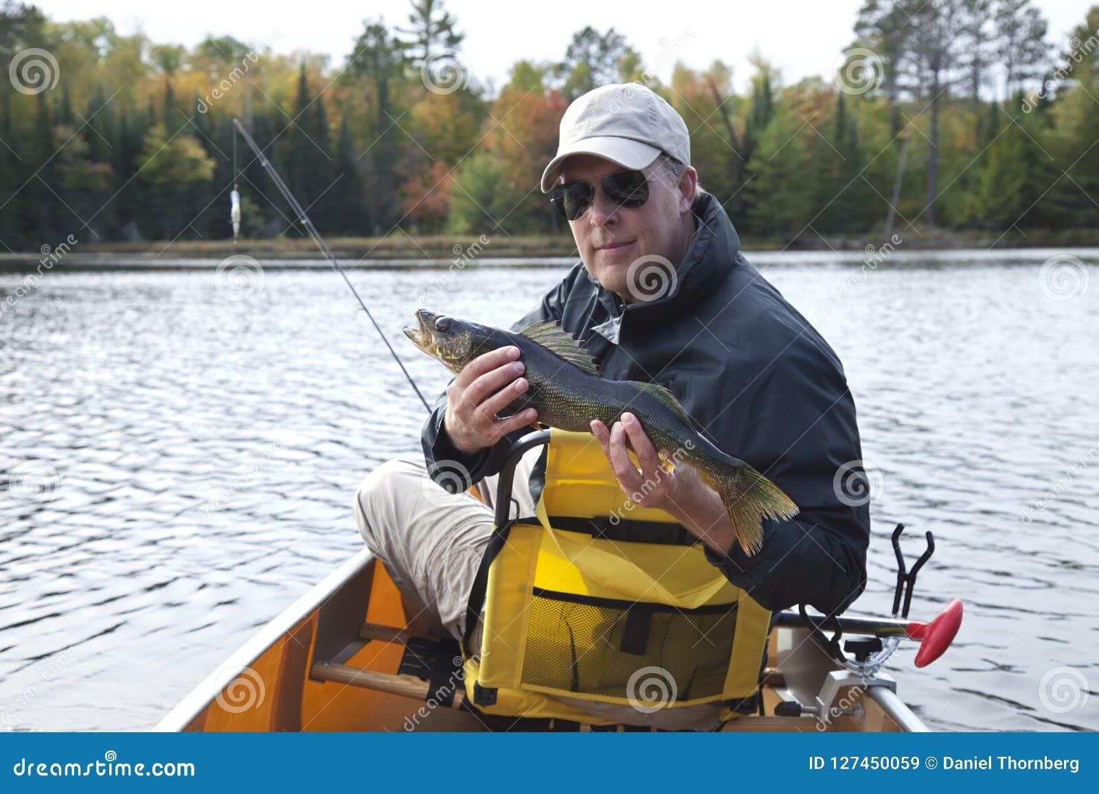 Uśmiechnięty rybak w czółnie na Minnestoa jeziora północnych chwytach