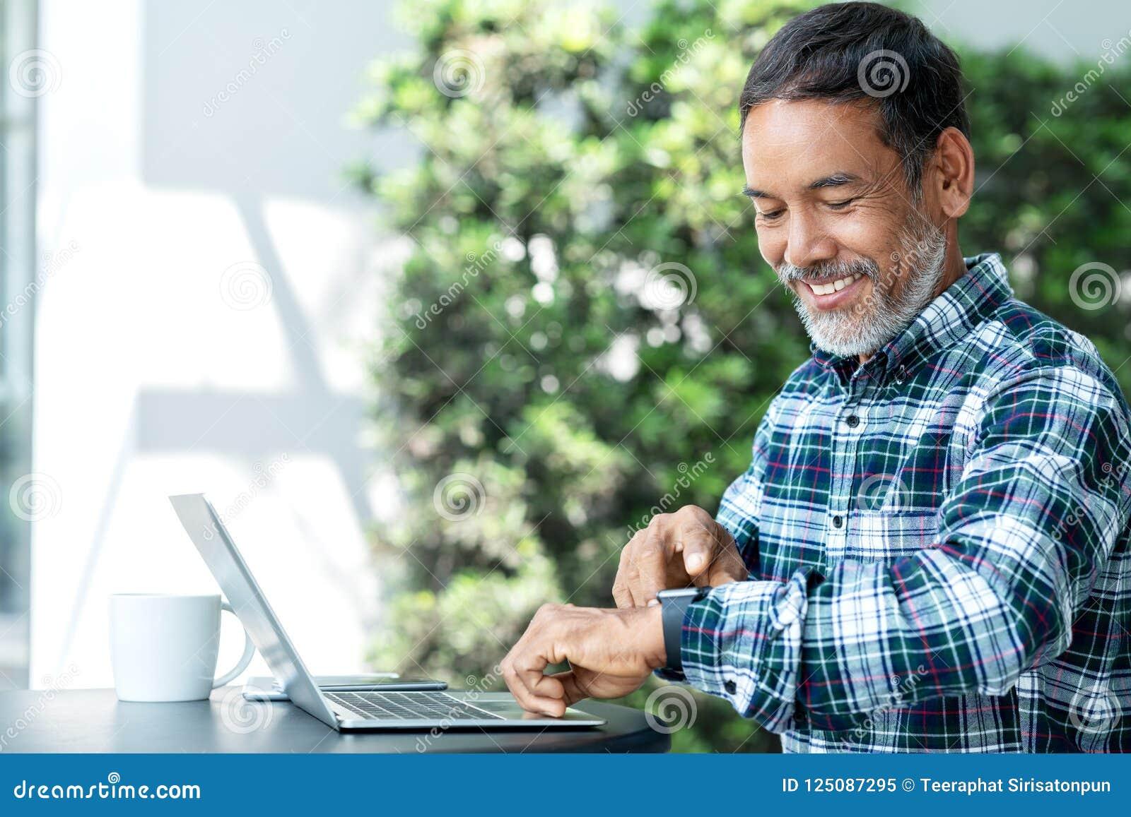 Uśmiechnięty szczęśliwy dojrzały azjatykci mężczyzna z białą elegancką krótką brodą używać cyfrowego smartwatch i macania ekran p