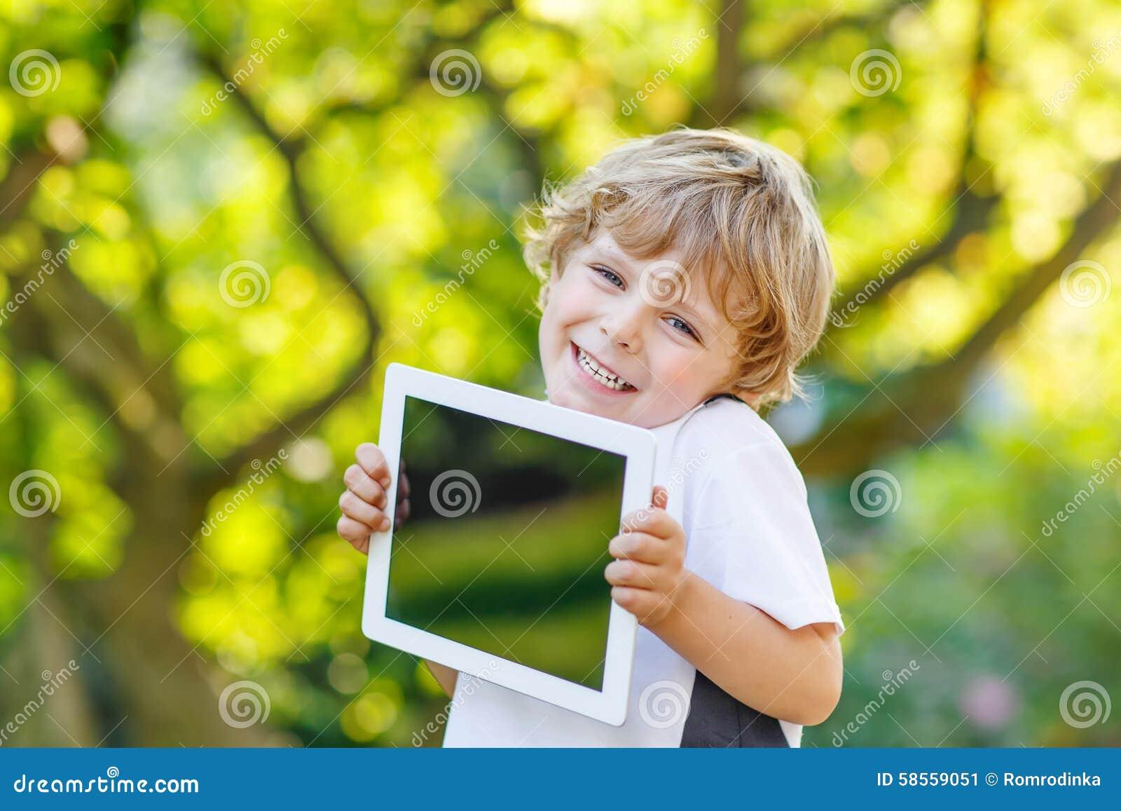 Uśmiechnięty szczęśliwy małego dziecka mienia pastylki komputer osobisty, outdoors