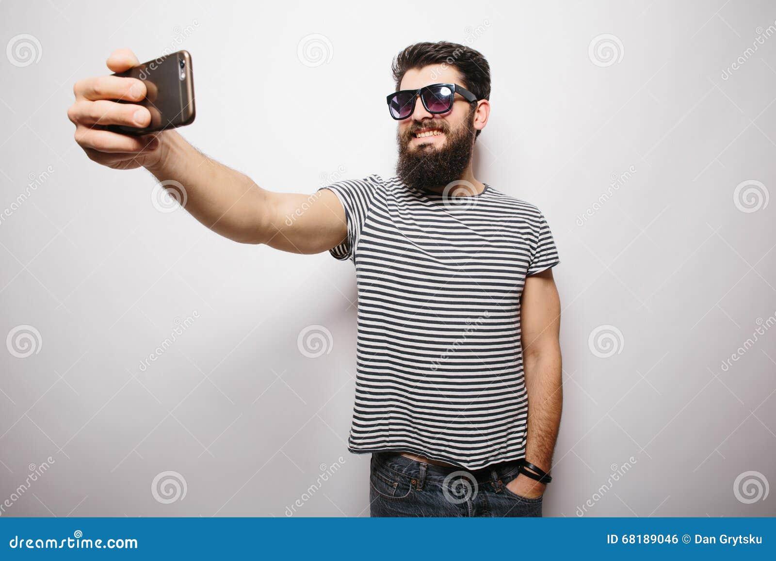 Uśmiechnięty szczęśliwy modnisia mężczyzna w słońc szkłach z brodą bierze selfie z telefonem komórkowym