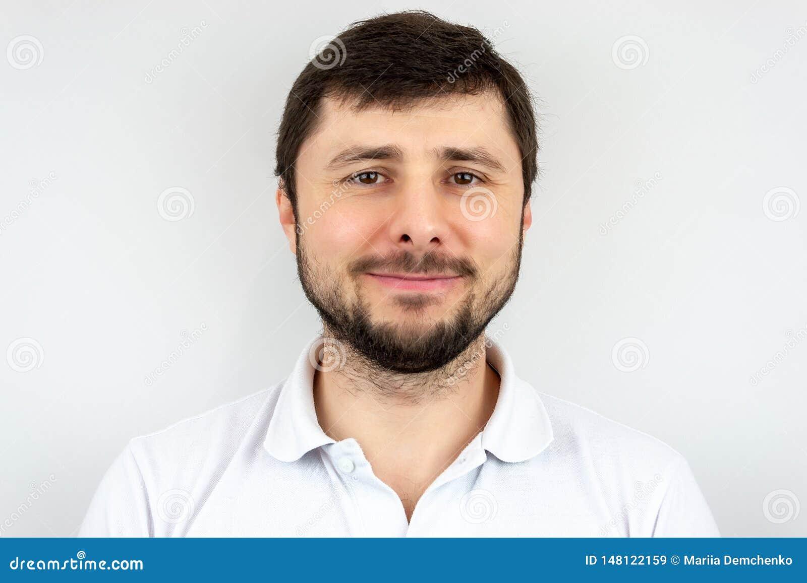 Uśmiechnięty szczęśliwy przystojny brodaty mężczyzna z brązem ono przygląda się w białej koszulce