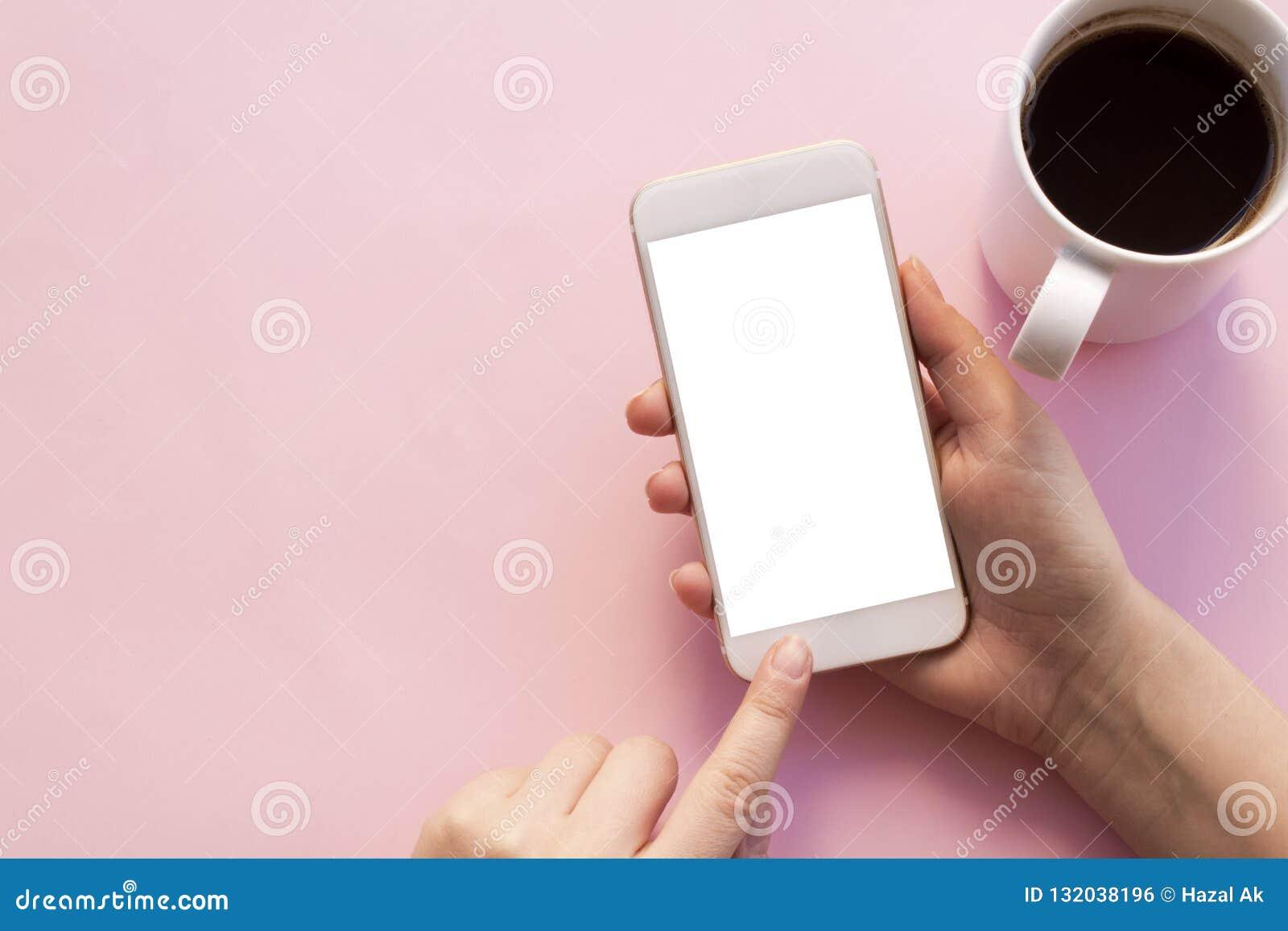 Używać telefon komórkowego trzyma filiżankę