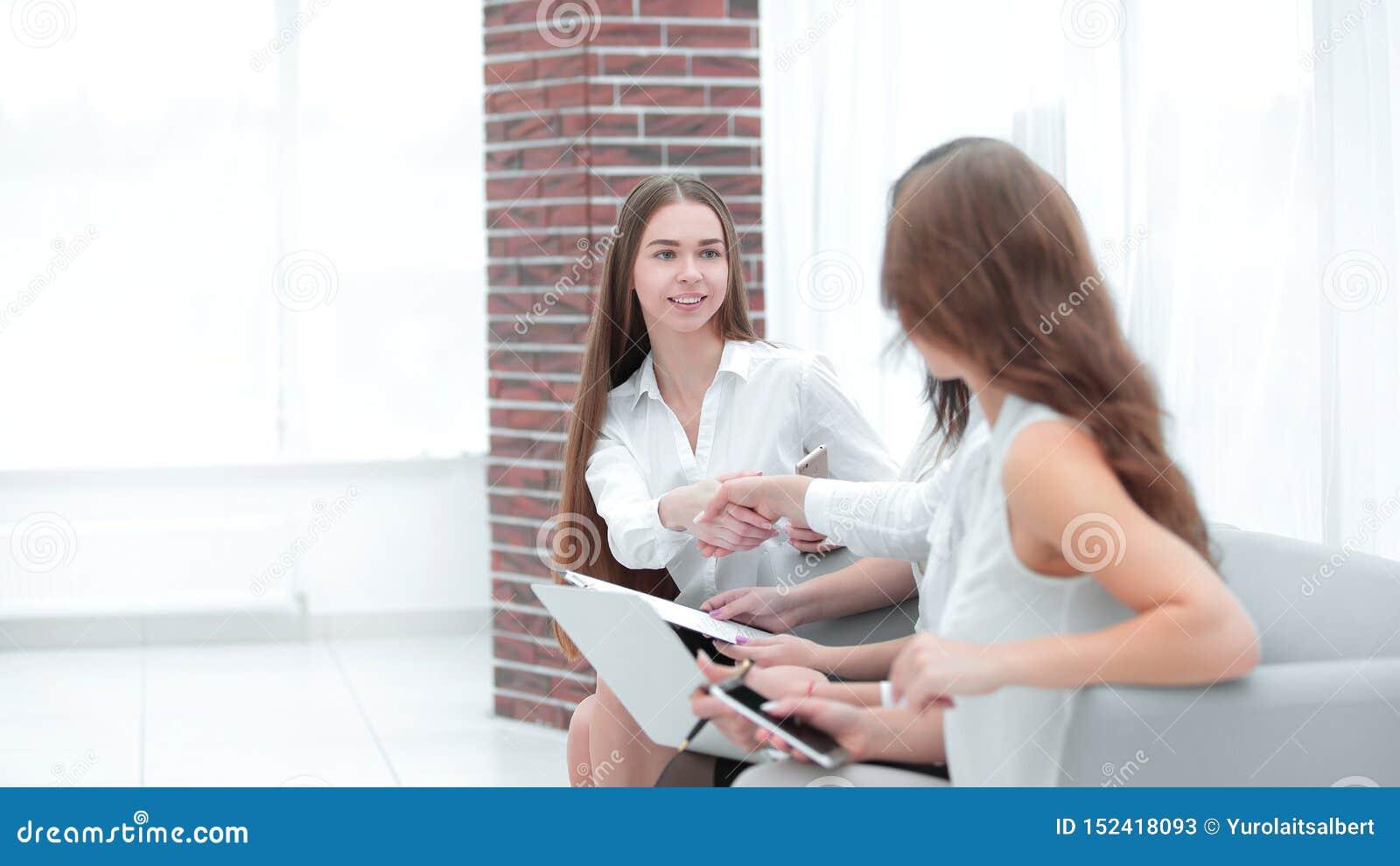 U?cisk d?oni dwa biznesowej kobiety siedzi w biurowej sali