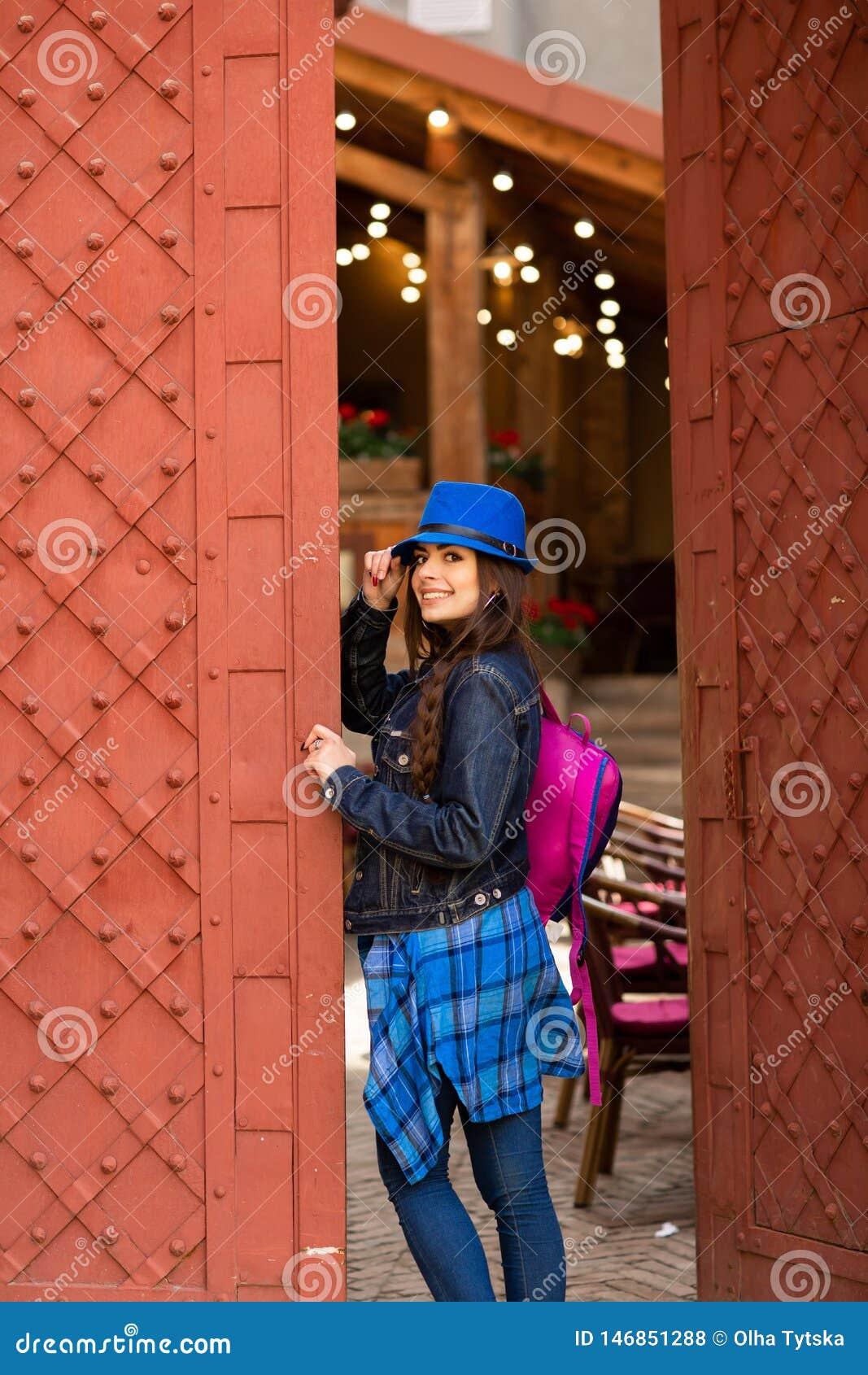 U?miechni?ta ?adna dziewczyna w b??kitnym kapeluszowym pobliskim starym budynku z antykwarskimi czerwonymi drzwiami kobiety model