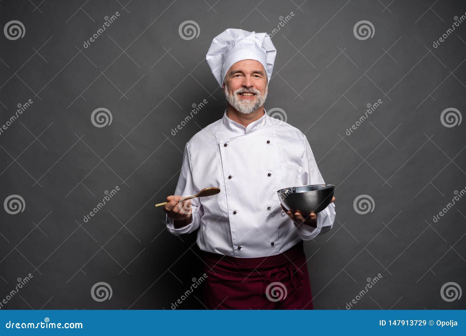 U?miechni?ty dojrza?y m?ski szef kuchni z pucharem i kulinarnym vane w r?kach na czarnym tle