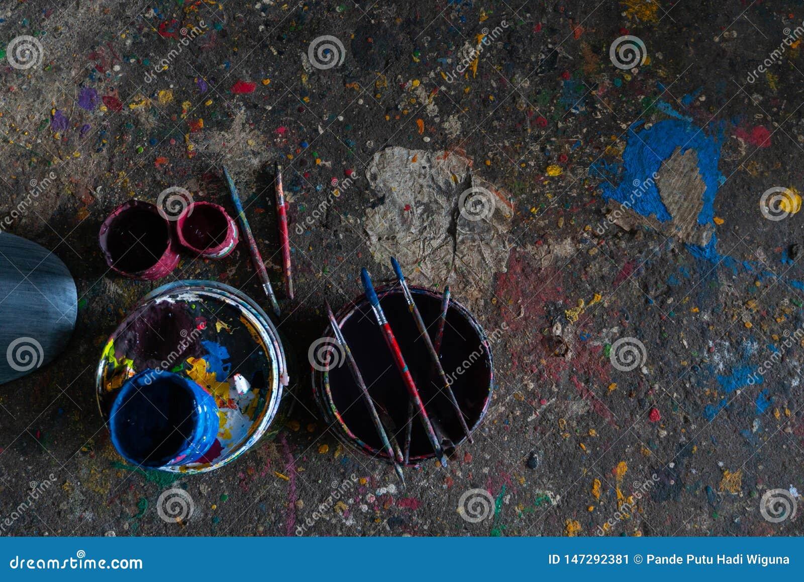 UBUD/BALI-APRIL 27 2019年:有刷子和地板的五颜六色的油漆桶充满美好的单色,因为油漆