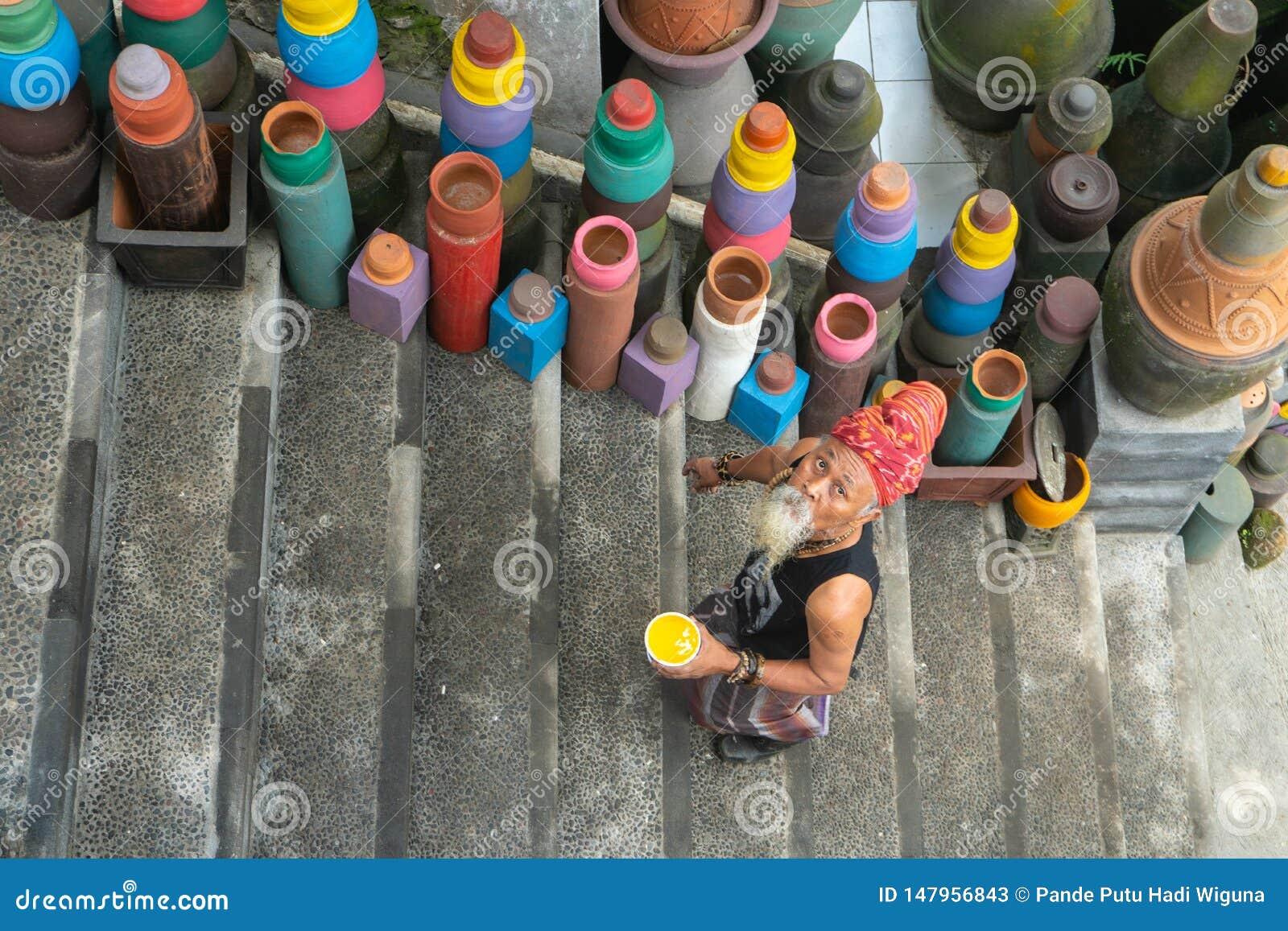 UBUD, BALI 27 APRILE 2019 un artigiano dalla barba bianca anziano delle terraglie che indossa un legame capo etnico sta colorando