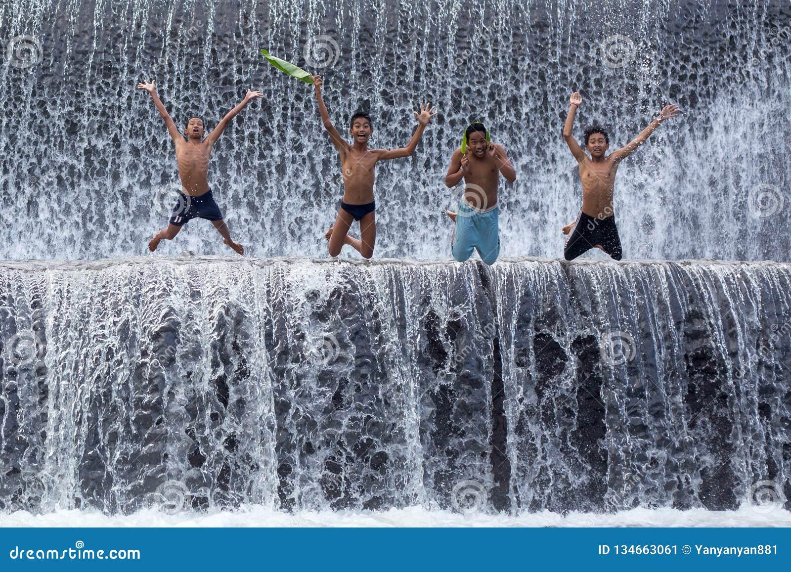 Poverty boys having fun at Tukat Unda dam, Bali
