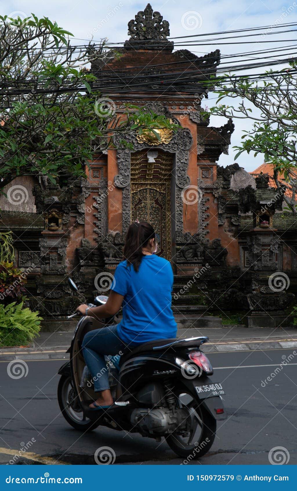 Ubud, Bali, Indonezja Maj 3, 2019: Niezidentyfikowana kobieta jedzie motorową hulajnogę w Ubud, Bali, Indonezja