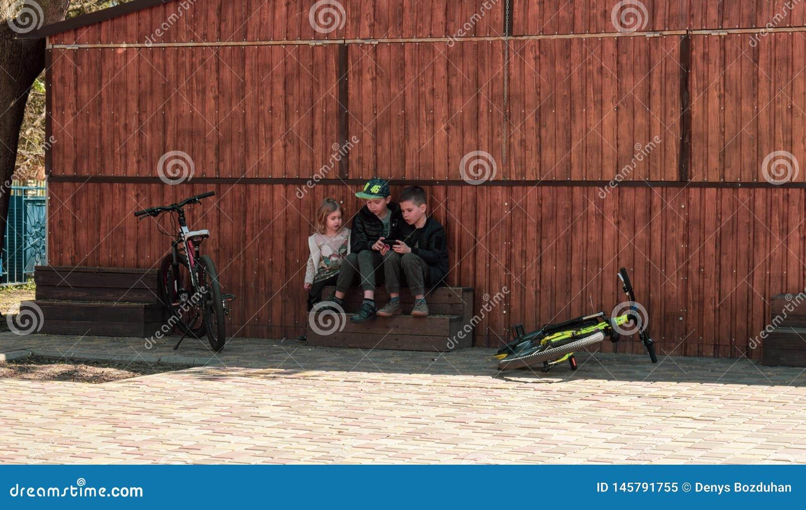 Ucrania, Kremenchug - abril de 2019: Los niños son el usar los smartphones en vez de las bicicletas que montan