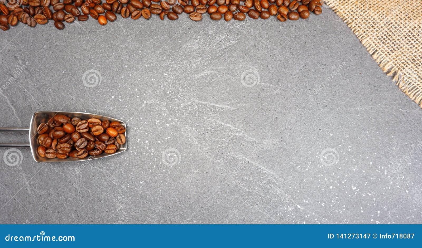 Uczciwy handel kawowe fasole z burlap i łyżką przy popielatym kuchennym worktop tłem