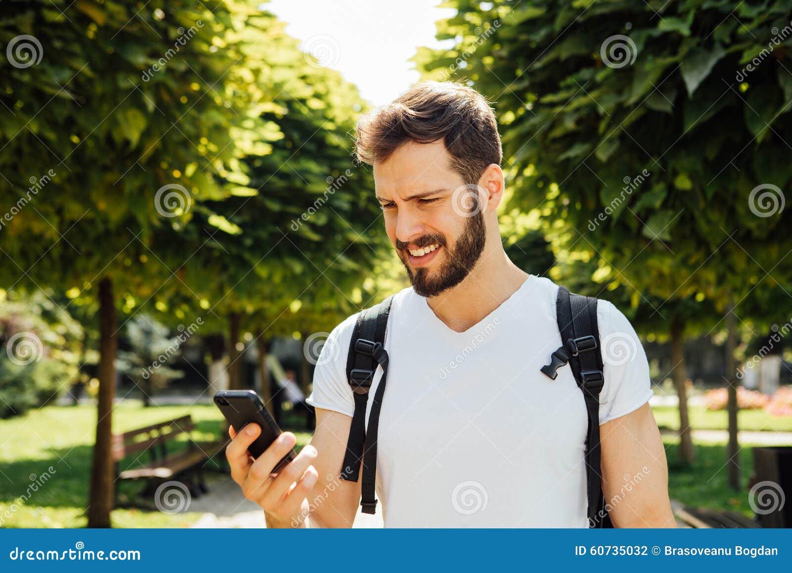Uczeń opowiada przy telefonem komórkowym z plecakiem