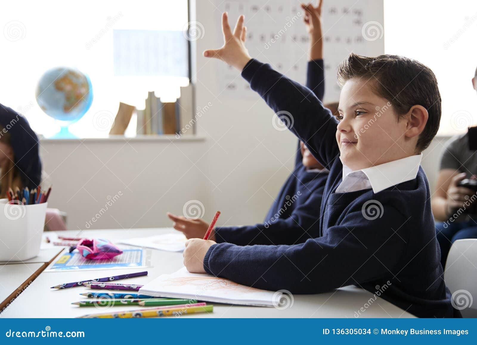 Uczeń podnosi jego rękę w szkoły podstawowej klasie z puszka syndromu obsiadaniem przy biurkiem, zakończenie w górę, boczny widok